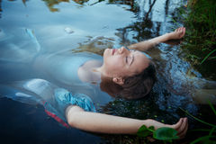 Young beautiful drowned woman in blue dress lying in the river Stock Photo