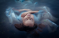 Young beautiful drowned woman in blue dress lying in the water Royalty Free Stock Image