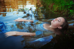 Young beautiful drowned woman lying in the water Stock Photography