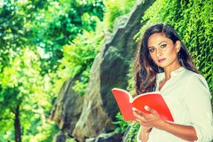 Young Beautiful East Indian American Woman with long hair reading red book outdoor at Central Park, New York. Wearing white shirt, standing by rocks with long stock photo