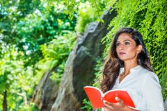 Young Beautiful East Indian American Woman with long hair reading red book outdoor at Central Park, New York. Wearing white shirt, standing by rocks with long royalty free stock photo