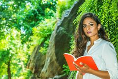 Young Beautiful East Indian American Woman with long hair relaxing outdoor at Central Park, New York City. Young Beautiful East Indian American Woman with long stock photos