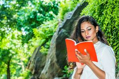 Young Beautiful East Indian American Woman with long hair relaxing outdoor at Central Park, New York City. Wearing white shirt, standing by rocks with long stock photography