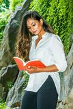 Young Beautiful East Indian American Woman with long hair relaxing outdoor at Central Park, New York City. Wearing white shirt, standing by rocks with long stock images