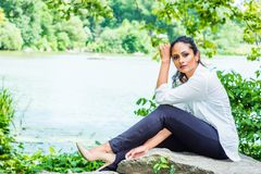 Young Beautiful East Indian American Woman traveling, relaxing at Central Park, New York. Wearing white shirt, black pants, high heels, sitting on rocks by stock photo