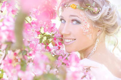 Young beautiful elegant, attractive girl standing in a forest near flowering tree with long hair blond in Sunny day and makeup. Among flowers with blue eyes Royalty Free Stock Photos