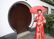 Young, beautiful and elegant Chinese woman wearing a typical Chinese bride`s silk red dress, adorned with golden phoenix and drago royalty free stock images