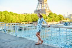 Young beautiful and elegant Parisian woman. In blue dress near the Eiffel tower in Paris Stock Photo