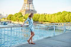 Young beautiful and elegant Parisian woman. In blue dress near the Eiffel tower in Paris Royalty Free Stock Photo
