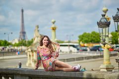 Young woman sitting near the Eiffel tower in Paris royalty free stock images