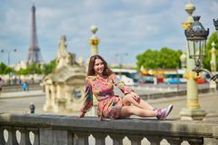 Young woman sitting near the Eiffel tower in Paris stock photos