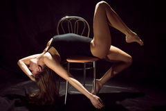 Young beautiful elegant seductive girl sexy woman in a black bodysuit performing on chair on black background Royalty Free Stock Photos