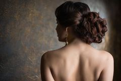Young beautiful elegant woman. In evening gold dress with beautiful hairdo Stock Photography