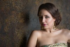 Young beautiful elegant woman. In evening gold dress with beautiful hairdo Royalty Free Stock Photography