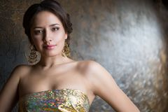 Young beautiful elegant woman. In evening gold dress with beautiful hairdo Stock Image