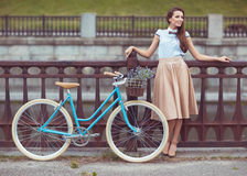 Young beautiful, elegantly dressed woman with bicycle Stock Photography