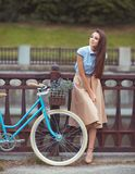 Young beautiful, elegantly dressed woman with bicycle Stock Photo