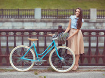 Young beautiful, elegantly dressed woman with bicycle outdoor Royalty Free Stock Image
