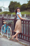 Young beautiful, elegantly dressed woman with bicycle outdoor Stock Photography