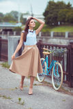 Young beautiful, elegantly dressed woman with bicycle outdoor Royalty Free Stock Images