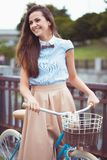 Young beautiful, elegantly dressed woman with bicycle in the par Stock Photos