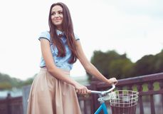 Young beautiful, elegantly dressed woman with bicycle in the par Royalty Free Stock Images
