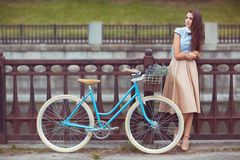 Young beautiful, elegantly dressed woman with bicycle in the par Royalty Free Stock Photography