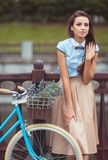 Young beautiful, elegantly dressed woman with bicycle in the par Stock Photo