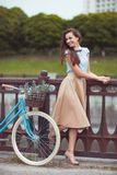 Young beautiful, elegantly dressed woman with bicycle in the par Stock Image