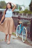 Young beautiful, elegantly dressed woman with bicycle in the par Stock Photography