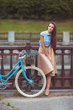 Young beautiful, elegantly dressed woman with bicycle, summer an Stock Photos