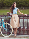 Young beautiful, elegantly dressed woman with bicycle Royalty Free Stock Photography