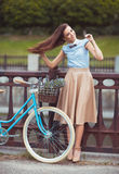 Young beautiful, elegantly dressed woman with bicycle Stock Images