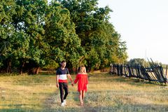 Young beautiful enamored couple walking outdoors in summer at sunset. 1 royalty free stock photos