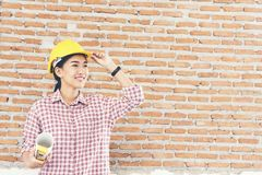 Young Beautiful engineer working holding building plans wear yellow helmet royalty free stock images