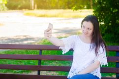 Young beautiful European brunette girl sitting on a bench and taking a picture of herself, makes selfie in a city park in a sunny stock images