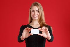 A girl holding between her fingers a business card and smiling. royalty free stock photography