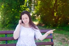 Young beautiful european girl sitting on a bench and talking on the phone. The girl points a finger away, gives advice and directi royalty free stock photo