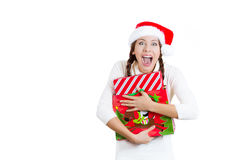 Young beautiful excited happy woman in red christmas hat looking satisfied with present she received Royalty Free Stock Photo