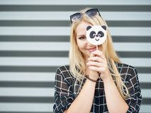 Young beautiful excited woman with gorgeous natural lips, blue and brown eyes in black blouse having fun with panda lollipop on ur Stock Photo