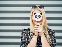 Young beautiful excited woman with gorgeous natural lips, blue and brown eyes in black blouse having fun with panda lollipop on ur Stock Photos