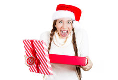 Young beautiful excited woman wearing red santa claus hat, opening gift box and super happy at what she gets Royalty Free Stock Images