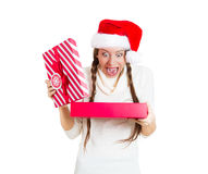 Young beautiful excited woman wearing red santa claus hat, opening gift box and super happy at what she gets Stock Photo