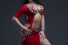 Young beautiful exotic eastern women performs belly dance in ethnic red dress on gray background. Young beautiful exotic eastern woman performs belly dance in Stock Photography