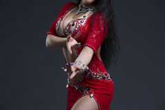 Young beautiful exotic eastern women performs belly dance in ethnic red dress on gray background. Young beautiful exotic eastern woman performs belly dance in Royalty Free Stock Photography