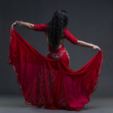 Young beautiful exotic eastern women performs belly dance in ethnic red dress with open back on gray background. Young beautiful exotic eastern woman performs Stock Photo
