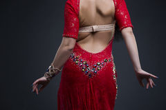 Young beautiful exotic eastern women performs belly dance in ethnic red dress with open back on gray background Royalty Free Stock Photos