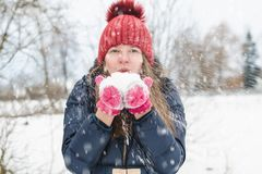 Young beautiful fair-haired girl blows snow from her hands in the park under soft fluffy snow on a cold winter day.  royalty free stock image