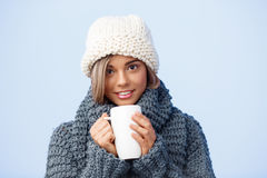 Young beautiful fair-haired girl in knited hat and sweater holding cup smiling looking at camera over blue background. Royalty Free Stock Photo
