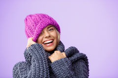 Young beautiful fair-haired girl in knited hat and sweater smiling winking looking at camera over violet background. Royalty Free Stock Photos